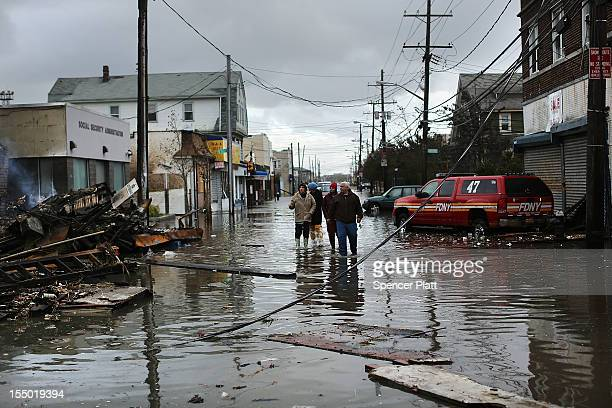 People look at homes and businesses destroyed during Hurricane Sandy on October 30, 2012 in the Rockaway section of the Queens borough of New York...