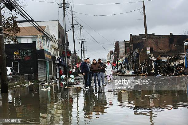 People look at homes and businesses destroyed during Hurricane Sandy on October 30 2012 in the Rockaway section of the Queens borough of New York...
