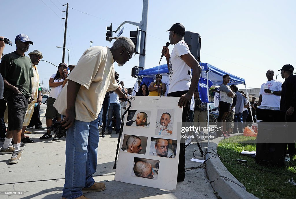 People look at hospital pictures of truck driver Reginald Denny during a rally near the intersection of Florence and Normandie Avenues in South Los Angeles on April 29, 2012 in Los Angeles, California. This intersection was site of where Denny was nearly beaten to death by a group of black assailants on April 29, 1992. It's been 20 years since the verdict was handed down in the Rodney King case that sparked the infamous Los Angeles riots.