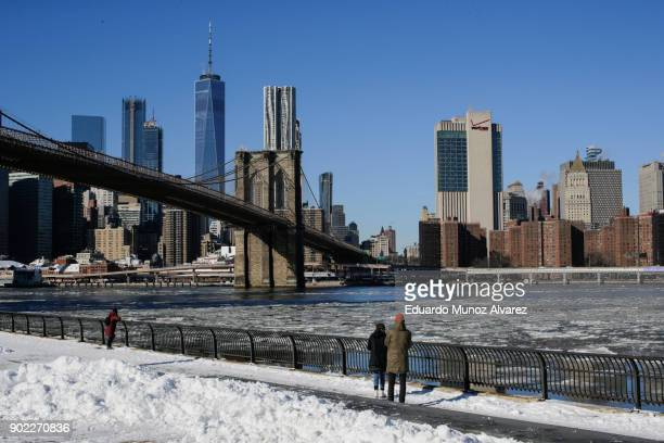 People look at ice floating along the East River as the skyline of New York City Brooklyn Bridge and One World Trade Center are seen during freezing...