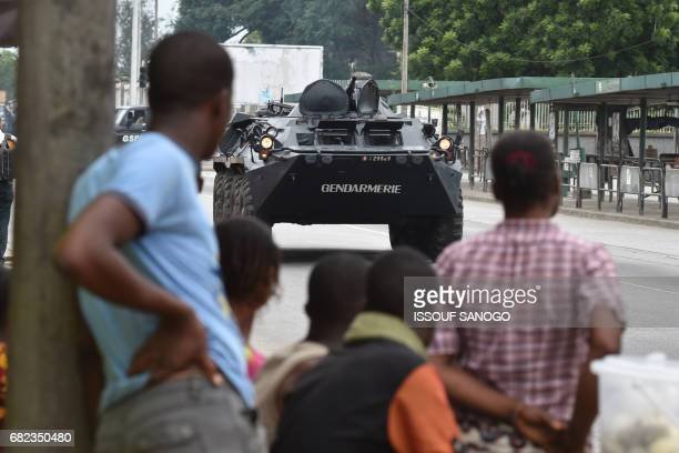 People look at Ivorian gendarmes as they patrol in their vehicle by Ivory Coast's army headquarters the Gallieni military camp in Abidjan on May 12...
