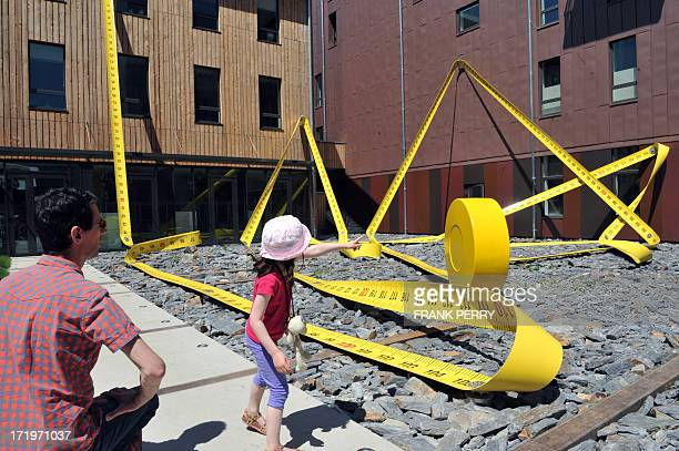 People look at Lilian Bourgeat's 'Tape Measure' a 136 metre oversized object one of the creations displayed in the centre of Nantes western France on...