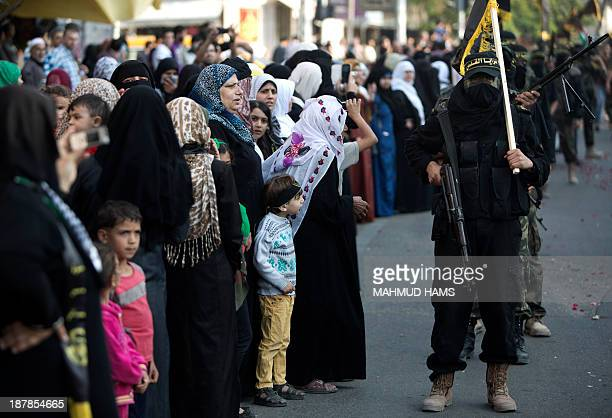 People look at members of the Palestinian Islamic Jihad movement parading with guns on November 13, 2013 in the streets of Gaza City during an...