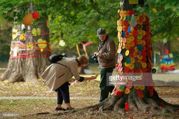 People look at messages attached by activists to some of the nearly 300 trees slated for removal in the Schlossgarten park next to Hauptbahnhof train...