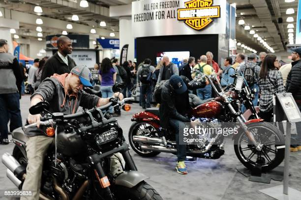 People look at motorcycles on the floor at the Progressive International Motorcycle Show at the Javits Center on December 1 2017 in New York City The...