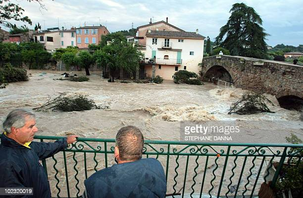 People look at Nartuby river in flood in the aftermath of flooding in a western district of the French south eastern city of TransenProvence on June...