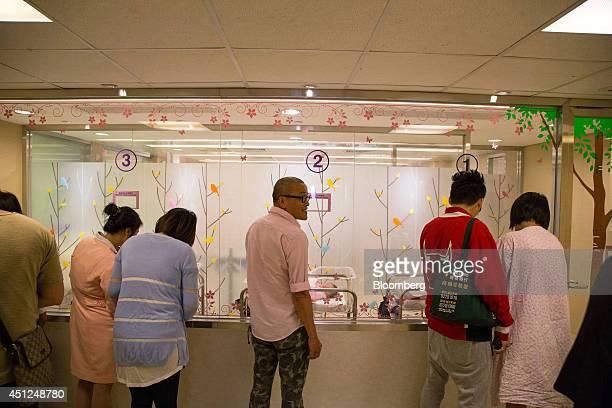 People look at newborn babies in the nursery at Hong Kong Baptist Hospital in Hong Kong China on Thursday June 26 2014 Discontent in Hong Kong has...