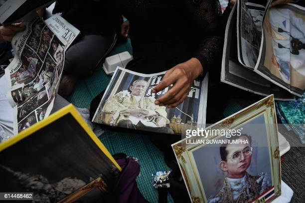 TOPSHOT People look at newspapers with images of the late Thai King Bhumibol Adulyadej at Siriraj Hospital in Bangkok on October 14 2016 Bhumibol the...
