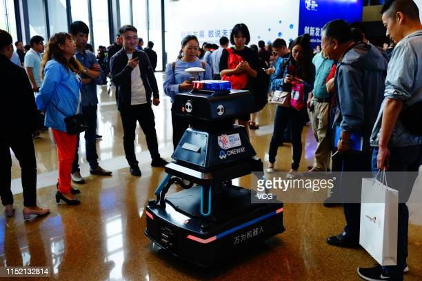 People look at Oneway security robot on the opening day of China International Big Data Industry Expo 2019 at Guiyang International Conference and...