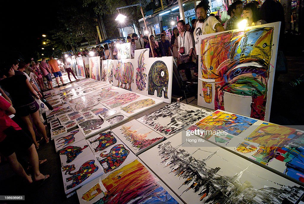 People look at paintings at Chiang Mai Sunday Market on November 25, 2012 in Chiang Mai, Thailand. The Chiang Mai Sunday Market, also called walking Street Market, is held from 4:00 pm until midnight and starts at Thapae Gate, running along the length of Ratchadamnoen Road through the heart of the Old City and is a Chiang Mai institution. Many of the stallholders have personally made the items they sell and the many hand crafted objects are a testimony to the skills and inventiveness of local people, which attracts local citizens and foreign tourists.