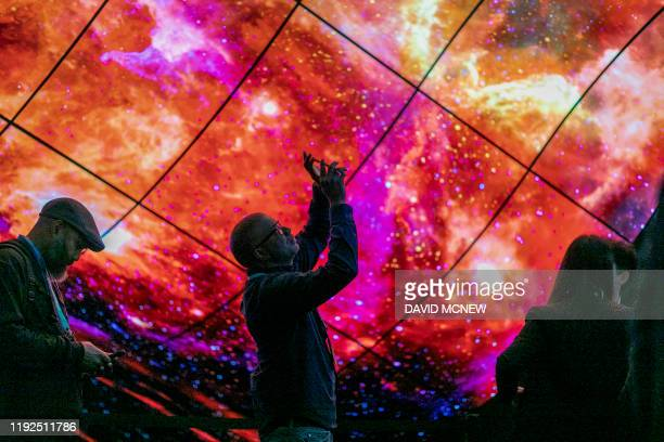 People look at panel of curved LG OLED televisions on opening day of the 2020 Consumer Electronics Show in Las Vegas Nevada on January 7 2020
