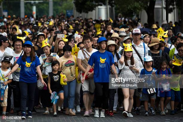 People look at performers dressed as Pikachu a character from Pokemon series game titles marching during the Pikachu Outbreak event hosted by The...