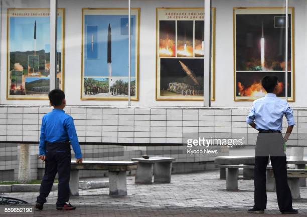 People look at photos of the firing of North Korea's intercontinental ballistic missile Hwasong14 in front of Pyongyang station on Oct 10 the 72nd...