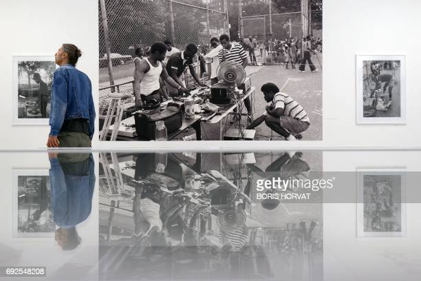 People look at pictures by US photographer Henry Chalfant Third Avenue the Bronx 1084 as they visit the exhibit ' Hip Hop un age d'or' at the...