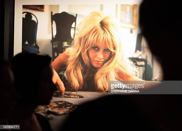 People look at pictures depicting French model and actress Brigitte Bardot on the eve of the Brigitte Bardot's exhibition opening at the Espace...