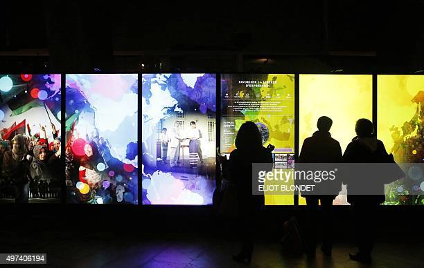 People look at pictures projected at the UNESCO headquarters on November 16 2015 in Paris during the celebration of the 70th anniversary of the...