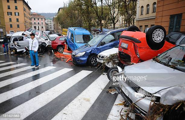 People look at piledup cars in the street after river Bisagno burst its banks during heavy rainfall on November 4 2011 downtown Genoa The Italian...