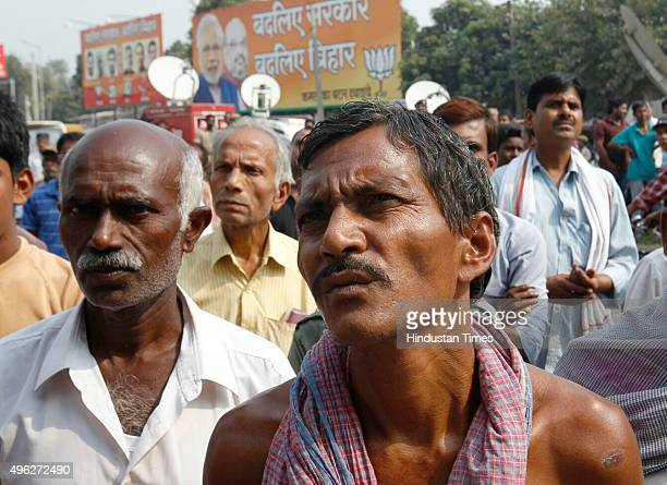 People look at poll results on screen showing negative BJP trends outside the party office on the vote counting day of the Bihar assembly elections...