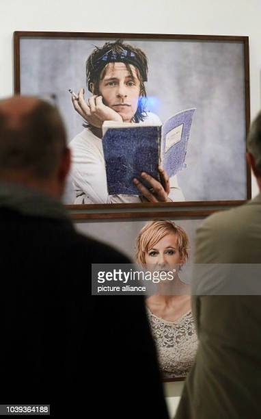 People look at portraits of actors Alexander Scheer and Susanne Lothar during the opening of the exhibition 'Stand der Dinge' in the art museum...