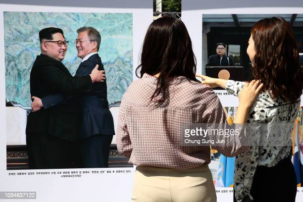 People look at posters advertising the summit between South Korean President Moon Jae-in and North Korean leader Kim Jong Un during a photo...