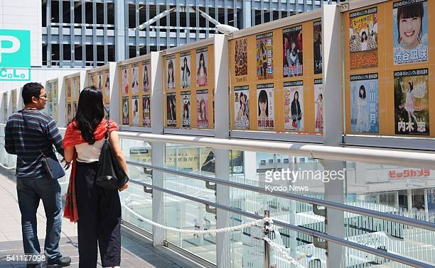 People look at posters of members of the AKB48 family of allgirl pop groups taking part in the annual popularity vote outside JR Niigata Station in...