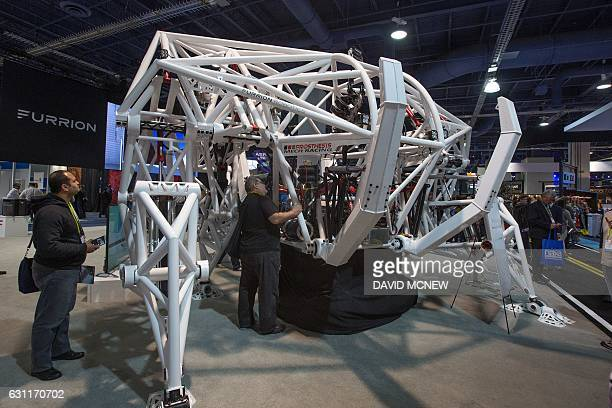 People look at Prosthesis a giant exobionic racing robot by Furrion Robotics during CES in Las Vegas Nevada January 7 2017 / AFP / DAVID MCNEW