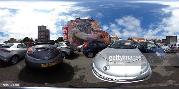 People look at secondhand cars offered for sale at a car dealer below artwork by Spanish artists Pichi Avo that is part of the 2016 Upfest on July 27...
