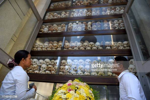 People look at skulls displayed in a stupa during the annual 'Day of Remembrance' at the Choeung Ek killing fields memorial in Phnom Penh on May 20...