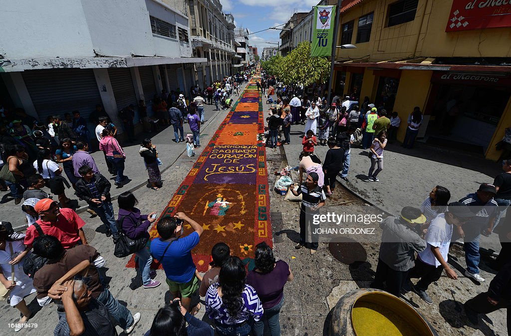 People look at the 1,400 meters carpet made with flowers and colored sawdust carried out by municipal employees and volunteers in an attempt to set a Guinness World Record for the longest carpet of the world, in Guatemala City on March 28, 2013. These carpets are traditionally made --separately-- during Hoy Week each year. AFP PHOTO / Johan ORDONEZ