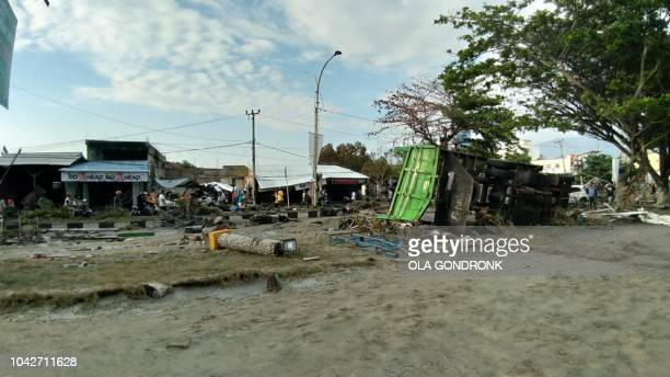 TOPSHOT People look at the aftermath of the tsunami in Palu on Sulawesi island on September 29 2018 Rescuers scrambled to reach tsunamihit central...