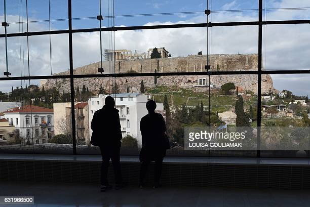 People look at the ancient Acropolis from the Parthenon hall of the Acropolis museum in Athens on January 18 2017 / AFP / LOUISA GOULIAMAKI