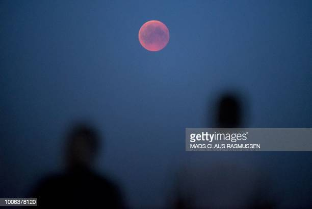 """People look at the """"blood moon"""" eclipse near Roskilde in Denmark, on July 27, 2018. - The period of total eclipse, when earth's shadow is directly..."""
