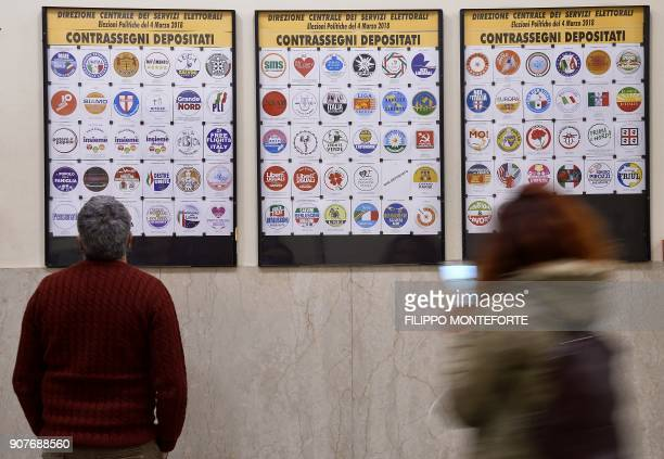 People look at the board bearing the parties logos registered at the Interior Ministry on January 20 2018 for the upcoming general elections to be...