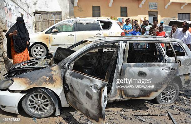 People look at the burnt out shell of a car following an explosion on July 6 2014 in central Mogadishu The Sunday morning car bomb explosion which...