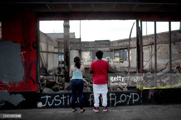 People look at the charred wreckage of a building destroyed during last week's rioting which was sparked by the death of George Floyd on June 2 2020...