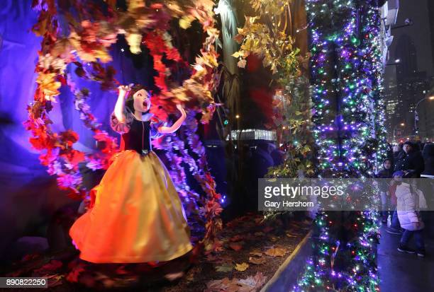 People look at the Christmas windows at the Saks Fifth Avenue store on 5th Avenue on December 9 2017 in New York City