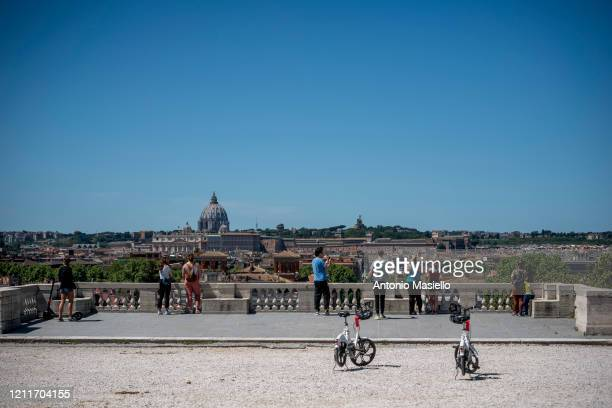People look at the city from the terrace of the Pincio in the Villa Borghese park during the first day of the so called phase two due to the...
