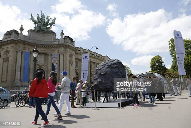 People look at the comet Tchouri and Philae robot replicas displayed near the Grand palais in Paris on May 10 2015 by the French National Centre for...