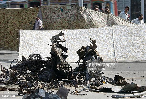 People look at the contorted car wreckage which was used in a suicide bombing in Karachi 10 May 2002 The wreckage is still lying on the spot of the...