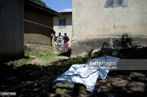 People look at the covered body of a neighbour suspected to have died of Ebola in Macenta on November 21 2014 The World Health Organisation said that...