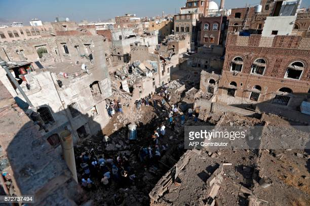 People look at the damage in the aftermath of an air strike in the Yemeni capital of Sanaa on November 11 2017 The Saudiled military coalition...