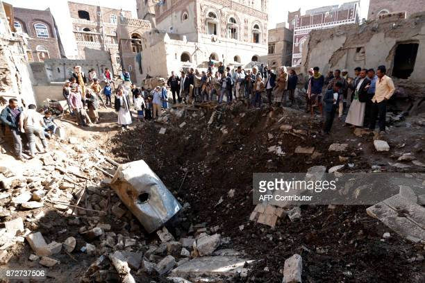 TOPSHOT People look at the damage in the aftermath of an air strike in the Yemeni capital of Sanaa on November 11 2017 The Saudiled military...