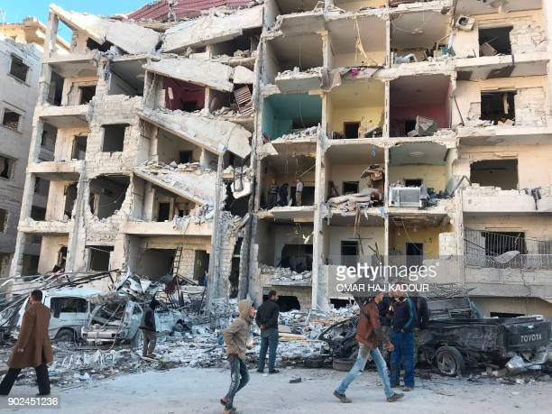 TOPSHOT People look at the damage in the aftermath of an explosion at a base for Asian jihadists in a rebelheld area of the northwestern Syrian city...