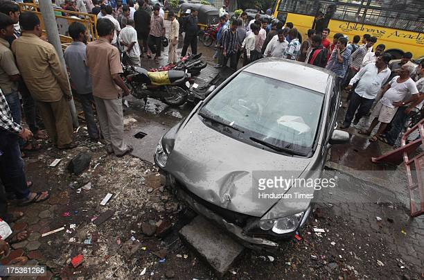 People look at the damaged car and bikes which met with an accident at Linking Road Kandivali on August 2 2013 in Mumbai India Indian TV actress and...