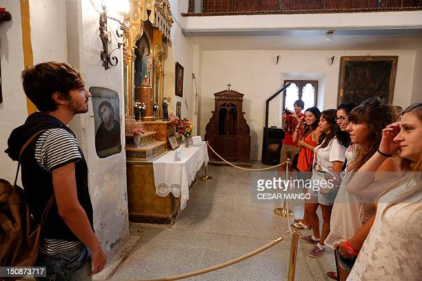 People look at the deteriorated version of 'Ecce Homo' by 19thcentury painter Elias Garcia Martinez at the Borja Church in Zaragoza on August 28 2012...