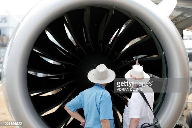 People look at the engine of an Embraer E190E2 aircraft displayed at the Farnborough Airshow south west of London on July 19 2018