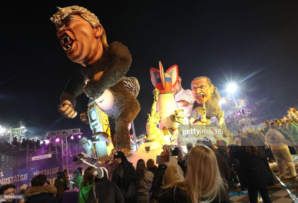 People look at the float 'Planet of the apes' depicting US President Donald Trump as it parades in the streets of Nice for the 134rd edition of the Nice Carnival in Nice, southeastern France on February 20, 2018. The 134th carnival runs from February 17 until March 3, 2018, and celebrates this year the 'King of Space'. /