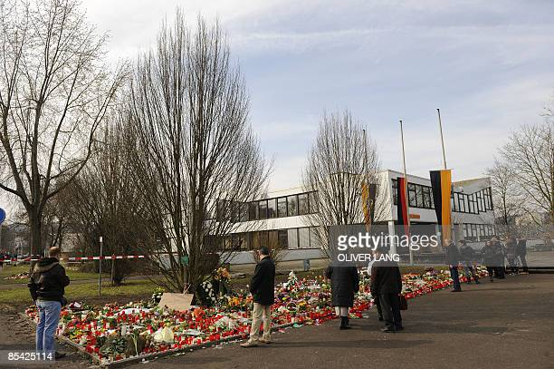 People look at the flowers and candles left in front of the Albertville secondary school in Winnenden southern Germany on March 14 2009 A teenager in...