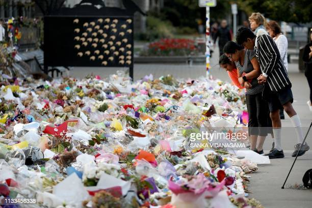 People look at the flowers and tributes displayed in memory of the twin mosque massacre victims at the Botanical Garden in Christchurch on March 29...