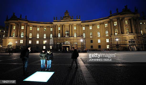 People look at the glass memorial by Michal Ullman for the Nazi book burning held on May 10 1933 on the Bebelplatz square in front of the Humboldt...